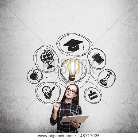 Nerd girl in dress standing near concrete wall with education sketches and glowing light bulb. Concept of career in education. Mock up