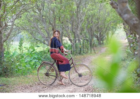Young asian women sitting on an old bike in tribe dress in rice field area.Thailand.
