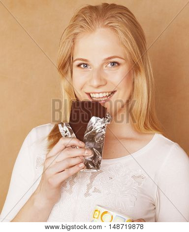 young cute blond girl eating chocolate and drinking coffee close up on warm background