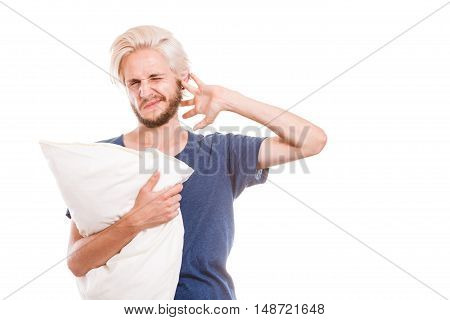 Health care sleep disorder concept. Sleepy tired guy holding pillow in one and closing his ear with another hand protecting from noise isolated on white