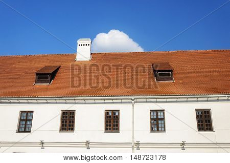 Old tiled roof with two attic windows and chimney in old part of Minsk Belarus