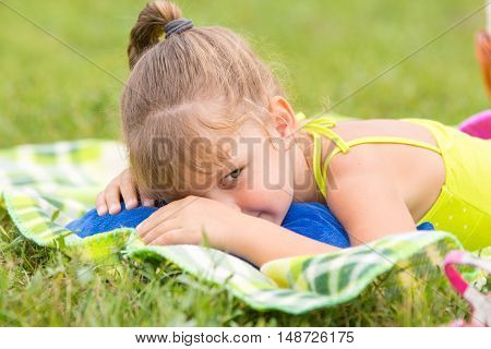 Five-year Girl Lies On A Bed On A Green Meadow And Artfully Looks Aside