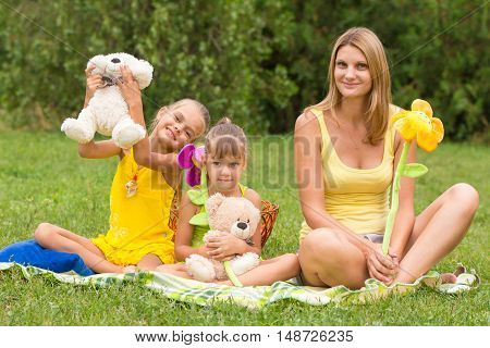 Mother And Daughter Sitting With Soft Toys On A Picnic