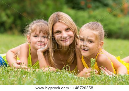 Mother And Two Daughters Lie On The Green Grass, And Looked Into The Frame