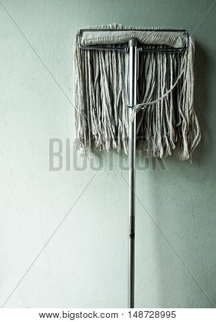 Close up dirty mop on wall background