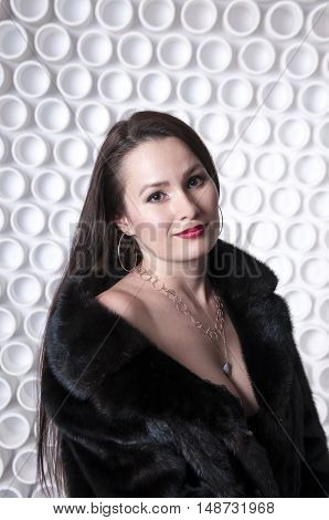Long-haired girl in a fur coat on the decorative background