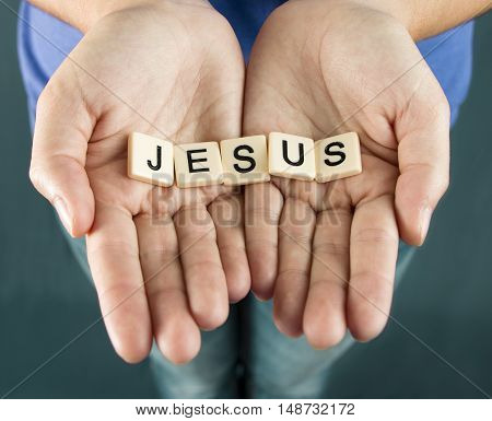 Jesus spelled in tiles being held by a young woman