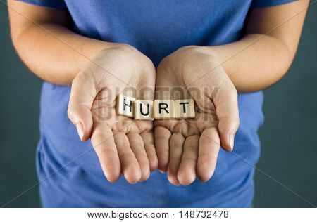 Hurt Spelled in Tiles in a young girls hands