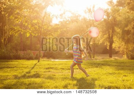 Little girl with a balloon runs on lawn in the park outdoors. Freedom and carefree.