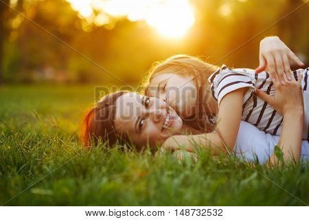 Mother and daughter lying on the lawn. Daughter kiss her mother on the cheek. Family in the city park outdoors. Happiness of motherhood and childhood. On the Sunset