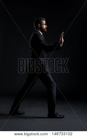Businessman pushing something imaginary over black background. Business and office concept.