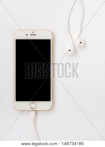CHIANGRAI THAILAND -SEPTEMBER 9 2016: Close-up image of new Apple iPhone 7 mockup connect with charging cable (Lightning) and Apple EarPods on white background with copy space.