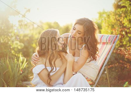 Two sisters. Girls talking in the garden. Family time. Human relationships.