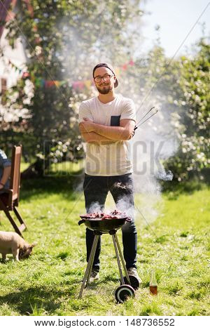 leisure, food, people and holidays concept - happy young man cooking meat on barbecue grill at outdoor summer party