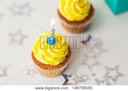 holiday, celebration, greeting and party concept - birthday cupcakes with burning candles