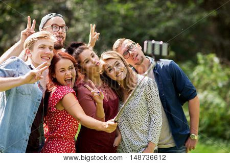 leisure, holidays, reunion, people and friendship concept - happy teenage friends taking picture by smartphone selfie stick at summer
