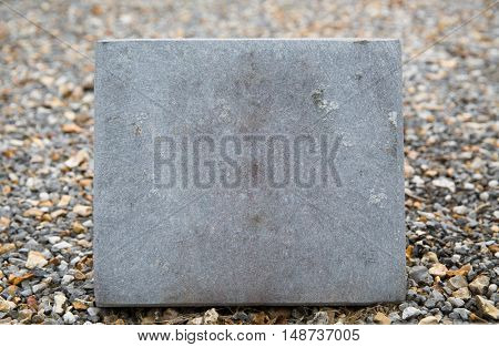 grave and burial concept - close up of old cemetery gravestone or memorial stone plate