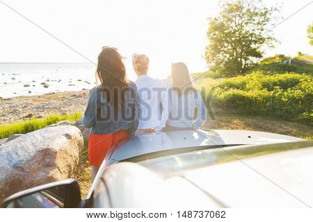 summer vacation, holidays, travel, road trip and people concept - happy teenage girls or young women near car at seaside
