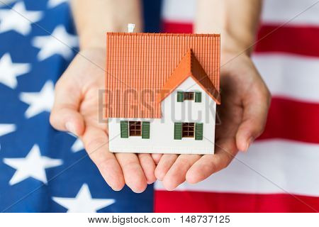 citizenship, residence, property, real estate and people concept - close up of hands holding living house model over american flag