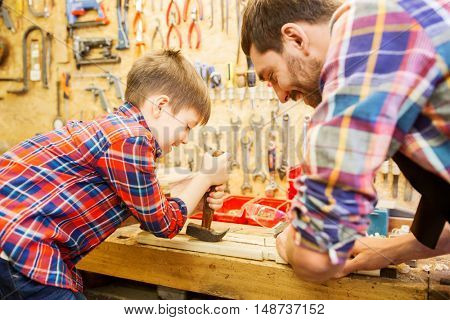 family, carpentry, woodwork and people concept - father and little son with claw hammer pulling nail out of wood plank at workshop