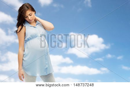 pregnancy, health, people and expectation concept - pregnant woman in bed touching her back and suffering from neckache over blue sky background