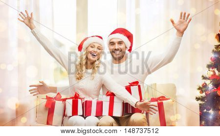 christmas, holidays and people concept - happy couple in santa hats with gift boxes sitting on sofa at home over lights