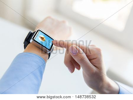 business, modern technology, media and people concept - close up of female hands setting smart watch with music player on screen at office