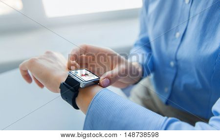business, technology, sport and people concept - close up of woman hands setting smart watch with fitness application at office