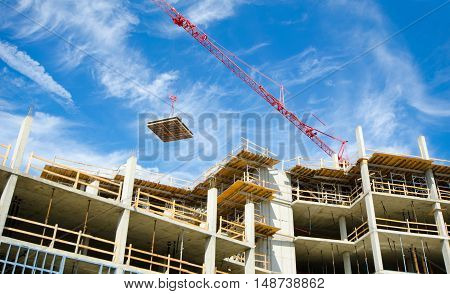 Concrete Highrise Construction site, with tower crane moving materials