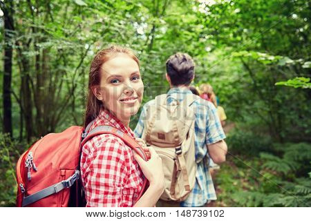 adventure, travel, tourism, hike and people concept - group of smiling friends walking with backpacks in woods
