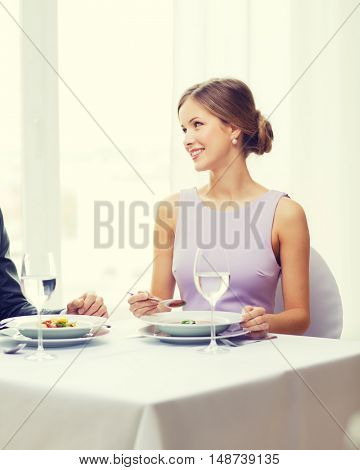 restaurant, couple and holiday concept - smiling young woman looking at husband or boyfriend while eating first course at restaurant