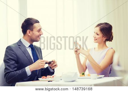 restaurant, couple, technology and holiday concept - smiling woman taking picture of husband or boyfriend while picturing sushi
