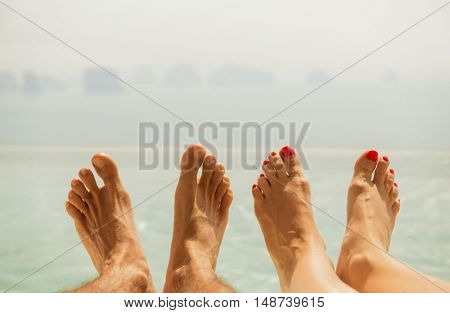 summer holidays, beach, travel, leisure and body care concept - closeup of couple feet over sea and sky on beach