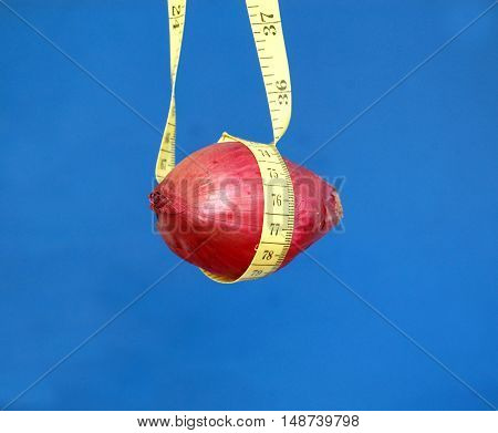 picture of a Red onion hanged on a tape measure