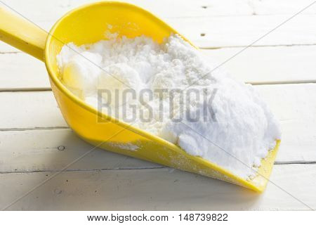 Dextrose in yellow shovel in hand on wooden white table.