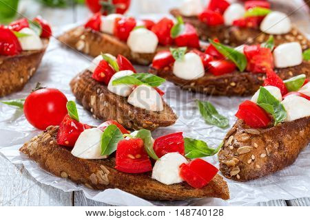 bruschetta with tomatoes mozzarella and basil on fried in olive oil rye baguette with seeds on parchment paper. close-up top view selective focus