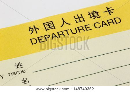 ShanghaiChina 09/25/2016 Chinese departure card in yellow close up on white to be filled out at the airport during immigration check when leaving China