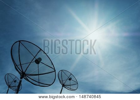 Silhouette, Satellite dish on blue sky with bright sun rays shining, communication technology network image background