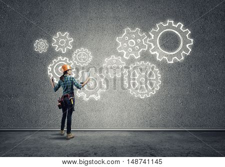 Back view of engineer woman in hardhat and sketched concept of teamwork on wall