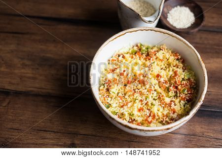 Vegetarian couscous salad made with bell pepper in a bowl, selective focus