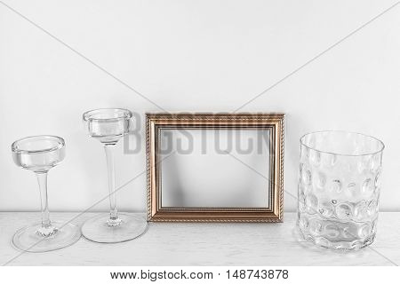 Photo frame, glass candlesticks and vase on table