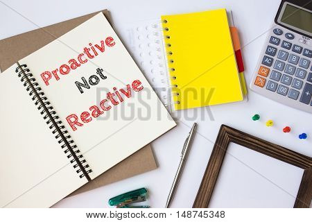 Text Proactive not reactive on white paper book on table / business concept
