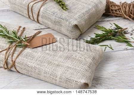 Closeup of two fabric wrapped Christmas presents on a rustic wood table.