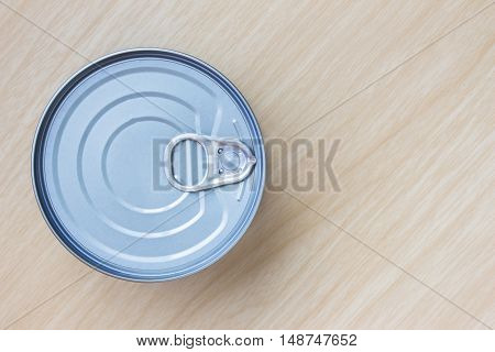 Tin can on wood table / top view