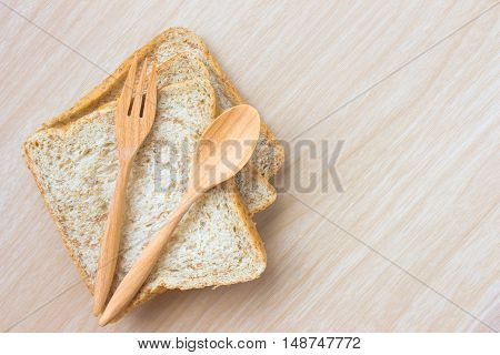 bread and wood spoon on wood table background / copy space / top view