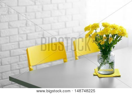 Bouquet of fresh yellow flowers on grey table