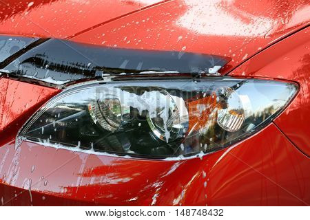 Car washing concept. Clean red car with foam, close up