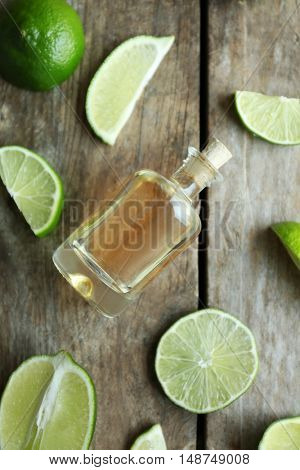Bottle with mint oil and sliced lemon on wooden background, top view