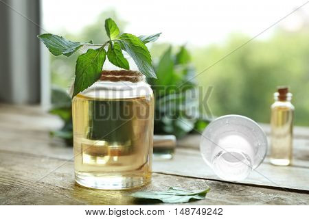 Bottle with mint oil and fresh leaves on blurred natural background