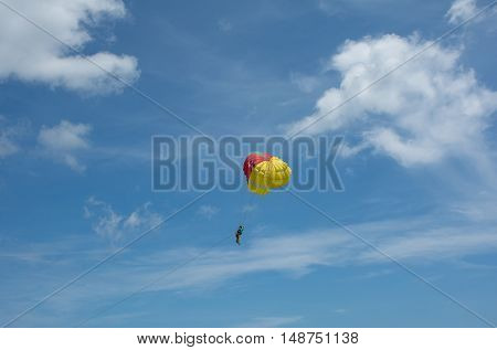Soft focused of Parachuting over sea towing by a speedboat with nice blue sky background at Patong beachPhuketThailand
